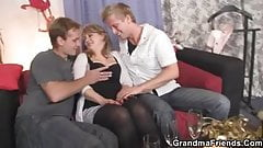 Mature woman in stockings swallows two cocks