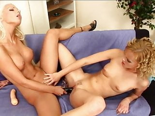 Gorgeous blonde girls share a black dildo in their holes