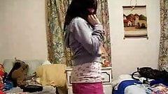 Busty brunette stripping in bedroom