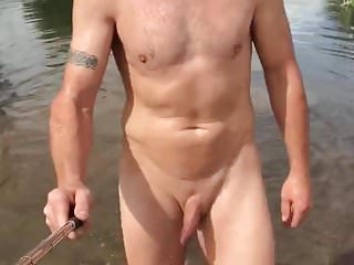 Nudist walking by river and skinny dipping