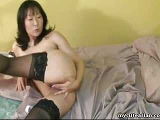 Asian mature woman in lust fingers her wet pussy
