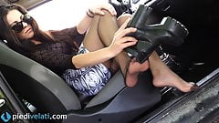 Brunette in black pantyhose shows off her feet from her car