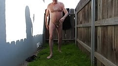 A naked daddy peeing in his backyard.