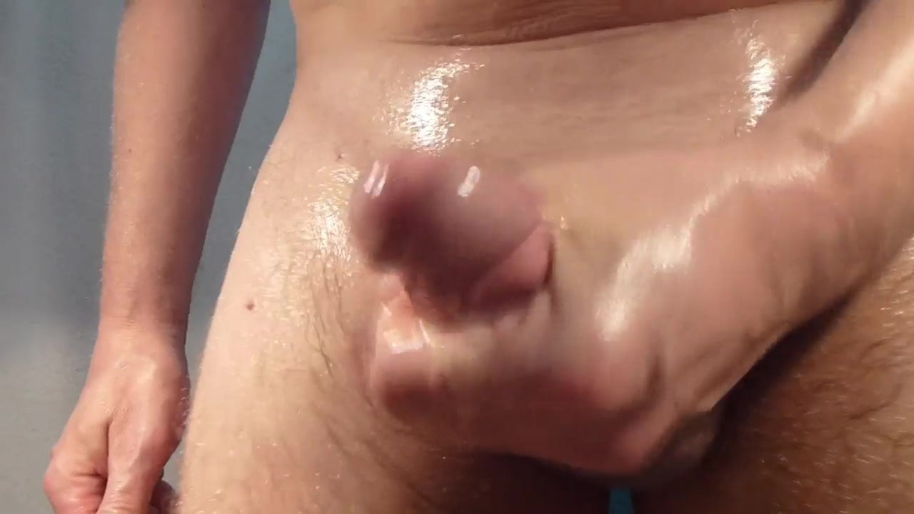Oiled up guy wanks his throbbing cock