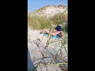 hommes se caresse a la plage devant inconnu