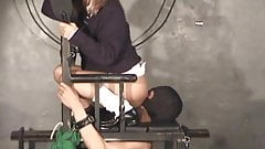 A slave bound by a chair and compellingly to cunnilingus