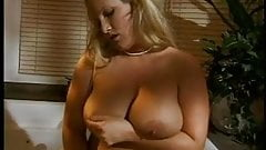 Pretty blonde with huge tits caresses her pussy and fondles her nipples