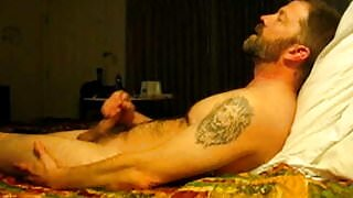 Hairy bear jacking on bed