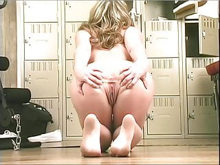 Beautiful blonde strips in the gym and fucks her shaved cunt with a big dildo