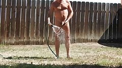 A naked daddy taking a hose shower in his backyard.