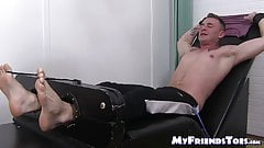 Inked young man has his feet and toes tickled by his friend