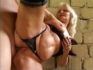 Guy fucks and facializes horny slut on an old tire on the ground
