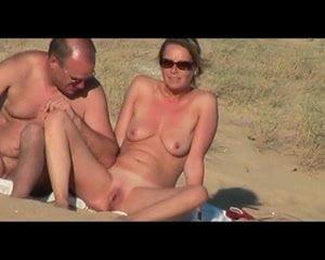 Elle écarte les jambes et exhibe sa chatte à la plage