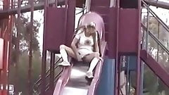 Hot blonde with large pussy lips upskirt peeing over a slide
