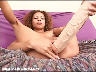 Curly haired petite babe feeds her pink pussy a huge dildo