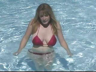 Busty brunette removes bikini to swim naked