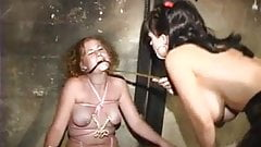 Curly redhead girl strapped tightly with a pink rope and has a gag ball