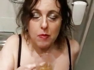 Mature in pantyhose drinks piss from a glass
