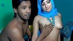 Mann praesentiert seine muslimische Ehefrau mit Kopftuch