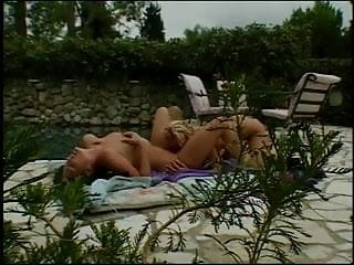 Brunette and blonde lesbians take turns licking their nipples and hairy pussy