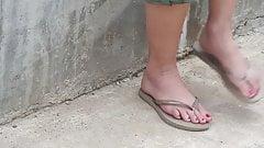 Cute girl dangling flip flops