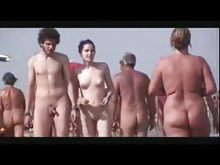 Pale sexy naked couple walk on nudist beach