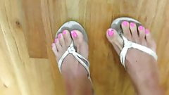 Bright pink nails and filthy white flip-flops