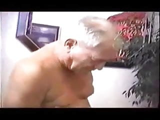 Gray haired grandpa and young boy sucking with each other