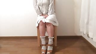 Girl in white dress sitting and squirming and losing control