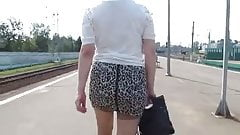 Girl in miniskirt and stockings going on a train station