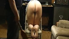 Spanking slave bare ass for punishment with paddle