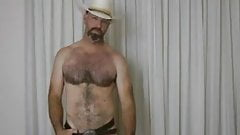 Cowboy polishes his belt buckle and squirts