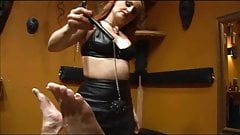 Mistress in leathers & nylons playing with her bound slave