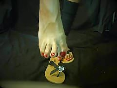 My feet in flip flops with red toes nails