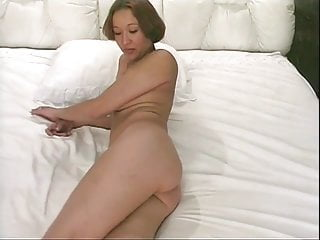Horny brunette strips and fingers her pussy in bed