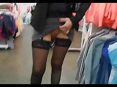 woman       shows her pussy full of piercing in a store