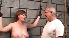 Slave gets leather cuffs on her wrists and master puts a whip on her tits
