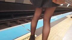 Sexy legs in shiny black pantyhose in metro