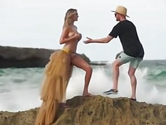 Kate Upton on the beach, washed of rock while topless