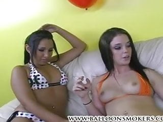 Two hot teens smoke cigarettes while showing off tits.