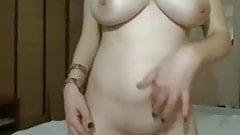 Long dark hair girl, big tits on bed stroking pussy
