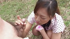 Japanese teen is on her knees sucking cock outdoors
