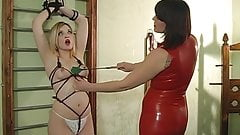 Super sexy chick in red latex bends blonde over her knee for a spanking