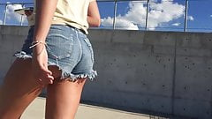 DW Brunette teen walking in cutoff jean shorts