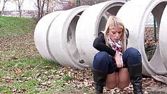 Blonde pisses on field behind concrete rings 25641