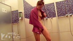 The naked sportswoman after training takes a shower.