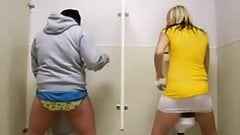 Two girls standing peeing in men's urinal 1