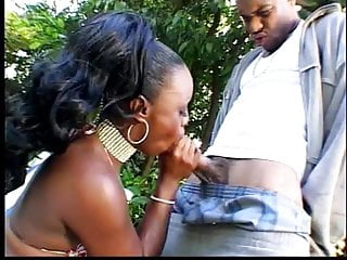 Busty black babe gets a long black cock to suck outside