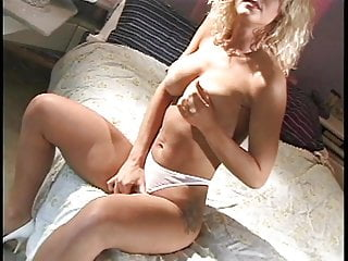 White whore takes off her white panties and masturbates on the bed