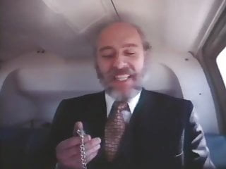 Old bearded man in a suit getting head in a helicopter